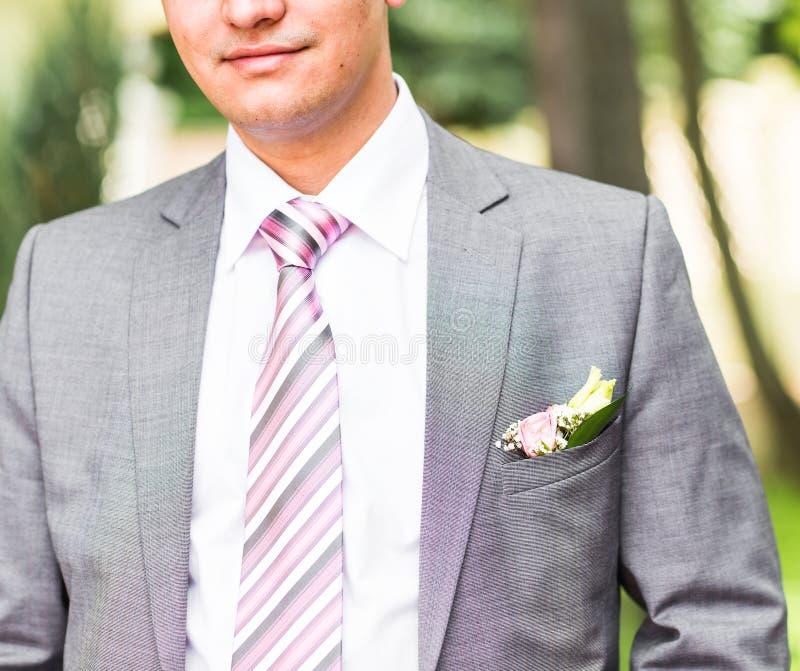 Knappe bruidegom bij huwelijkssmoking die en op bruid glimlachen wachten Gelukkig glimlachend bruidegomjonggehuwde De rijken verz stock foto