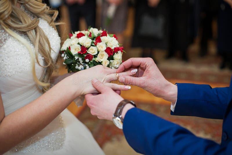 Knappe bruidegom die in blauw kostuum op trouwring op modieuze B zetten royalty-vrije stock fotografie