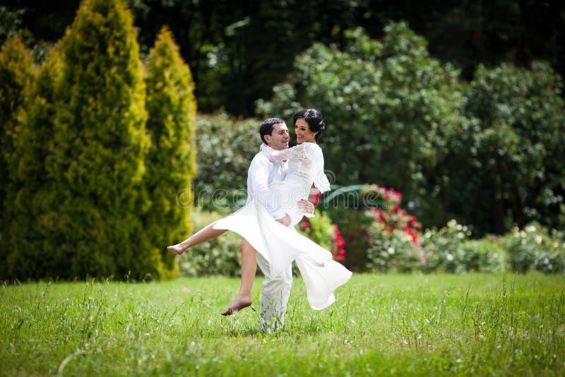 Knappe bruidegom die gelukkige bruid in zijn wapens in park houden stock afbeeldingen