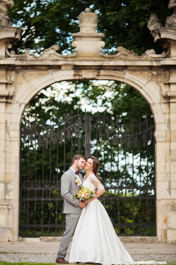 Knappe bruidegom die mooie bruid met boeket in romantisch Europees park koesteren royalty-vrije stock fotografie