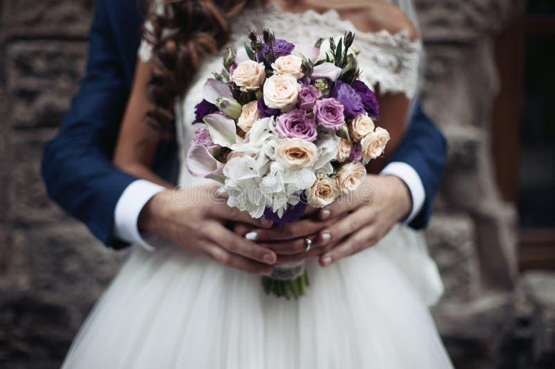 Knappe bruidegom die mooie bruid in witte kleding van behin koesteren stock foto's