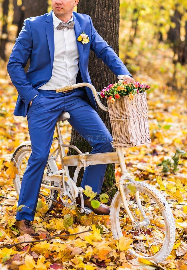 Knappe bruidegom en Uitstekende Fiets met bloemen op de achtergrond van het de herfstlandschap stock afbeelding
