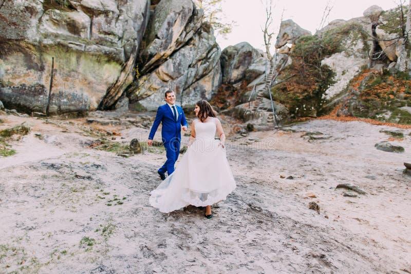Knappe bruidegom met zijn elegante nieuwe vrouw die op zandige opheldering lopen Prachtige rotsen als backround stock fotografie