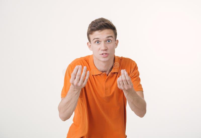 Knappe bruin-haired mens die oranje overhemd dragen die boos tonend handgebaar en sprekend iets razend over wit kijken royalty-vrije stock afbeeldingen