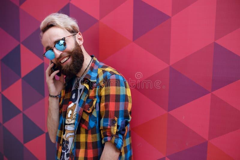 Knappe charismatische jonge mens die op mobiele telefoon, op een multicolore spreken backgound stock afbeelding