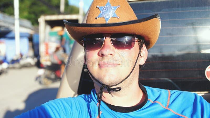 Knappe cowboy in hoed en zonnebril die in een pick-up in zonnige dag reizen royalty-vrije stock foto's