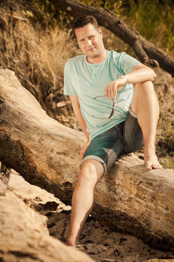 Knappe de mensenzitting van het manierportret op boom door overzees stock foto's