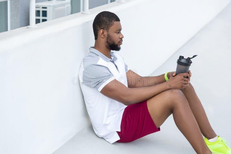 Knappe donker-haired jonge sportman die de afstand onderzoeken stock foto