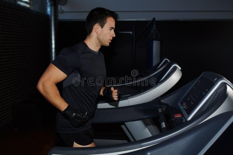 Knappe donkerbruine mens die training in gymnastiek doen die op tredmolen lopen stock afbeeldingen