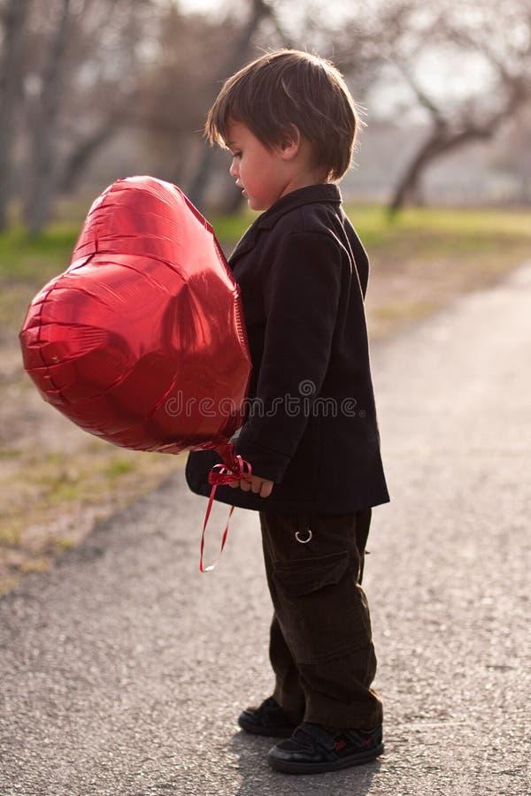 Knappe drie éénjarigenjongen met rode hartballon stock foto