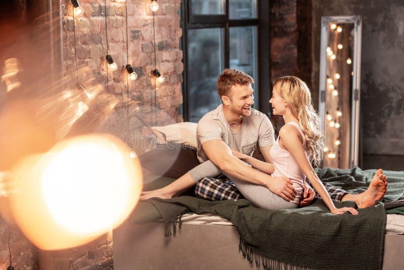 Knappe echtgenoot die zijn slanke aantrekkelijke vrouw in bed koesteren stock fotografie
