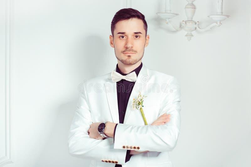 Knappe elegante bruidegom in wit kostuum royalty-vrije stock foto's