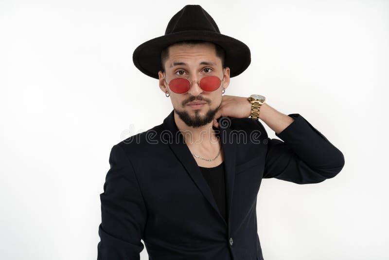 Knappe elegante gebaarde mens in zwart kostuum en hoed in ronde die zonnebril over witte achtergrond, copyspace wordt ge?soleerd  royalty-vrije stock afbeeldingen
