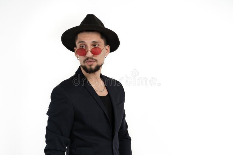 Knappe elegante gebaarde mens in zwart kostuum en hoed in ronde die zonnebril over witte achtergrond, copyspace wordt ge?soleerd  royalty-vrije stock foto's