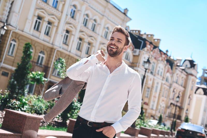 Knappe elegante jonge mens in het stedelijke plaatsen in Europese stad, het lopen stock foto's