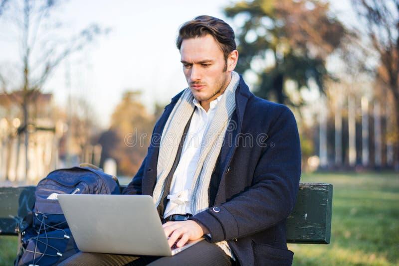 Knappe elegante zakenman die in een park werken stock afbeelding