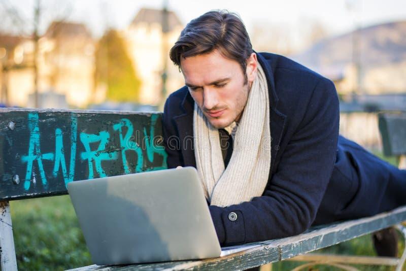 Knappe elegante zakenman die in een park werken stock afbeeldingen