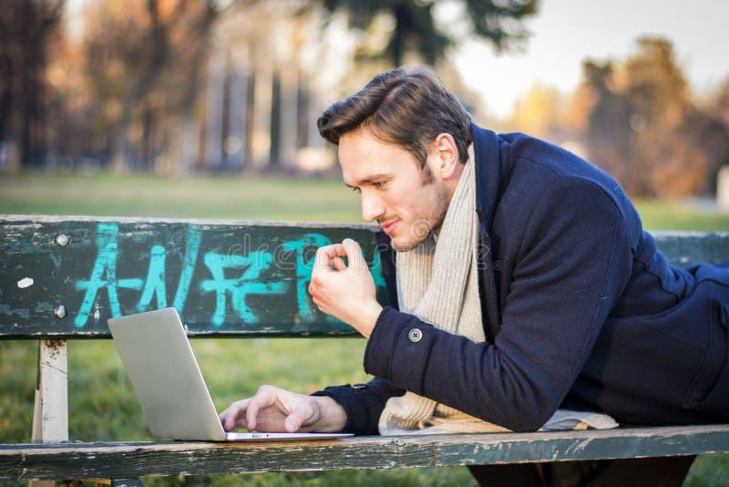 Knappe elegante zakenman die in een park werken royalty-vrije stock afbeeldingen