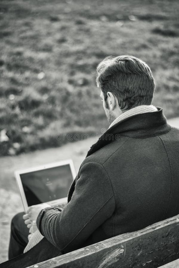 Knappe elegante zakenman die in een park werken royalty-vrije stock foto