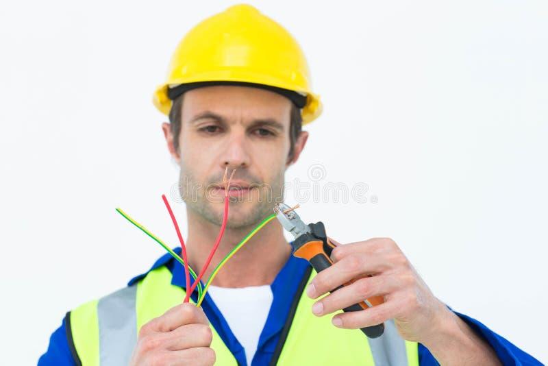 Knappe elektricien scherpe draad met buigtang stock foto's