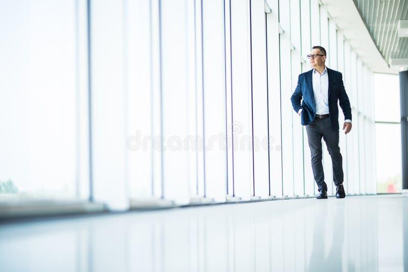 Knappe en succesvolle hogere bedrijfsmens die in modern bureaubinnenland lopen stock afbeeldingen