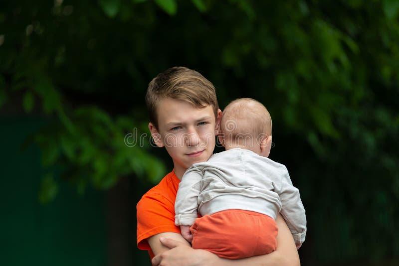 Knappe en volwassen jongen die een klein kind in zijn wapens houden, portret van een jonge gelukkige familie stock foto's