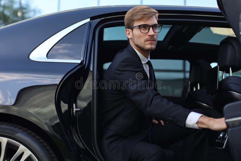 Knappe ernstige jonge zakenmanzitting in zijn comfortabele nieuwe auto en het gaan naar het bureau royalty-vrije stock fotografie