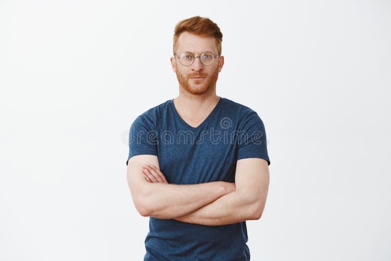 Knappe Europese zakenman met gemberhaar en varkenshaar in koele transparante glazen, die vingers op borst kruisen royalty-vrije stock foto