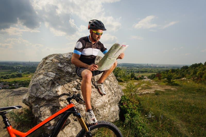 Knappe fietser met routekaart op de bovenkant van rots stock afbeelding