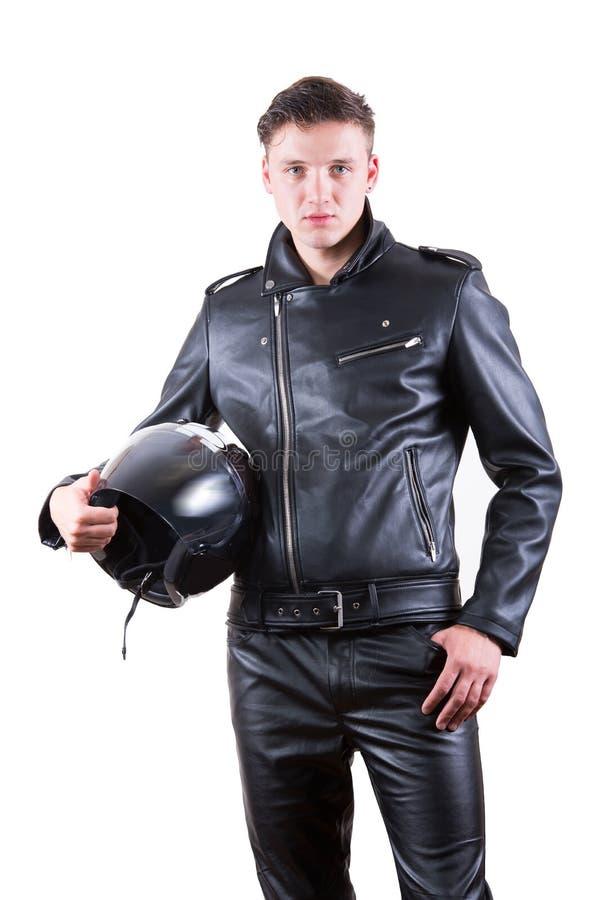 knappe fietsermens zwart leerjasje dragen en broek die motorfietshelm houden royalty-vrije stock foto's