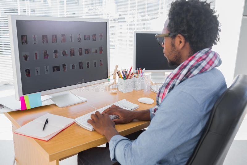 Knappe fotoredacteur die aan computer werken stock foto's