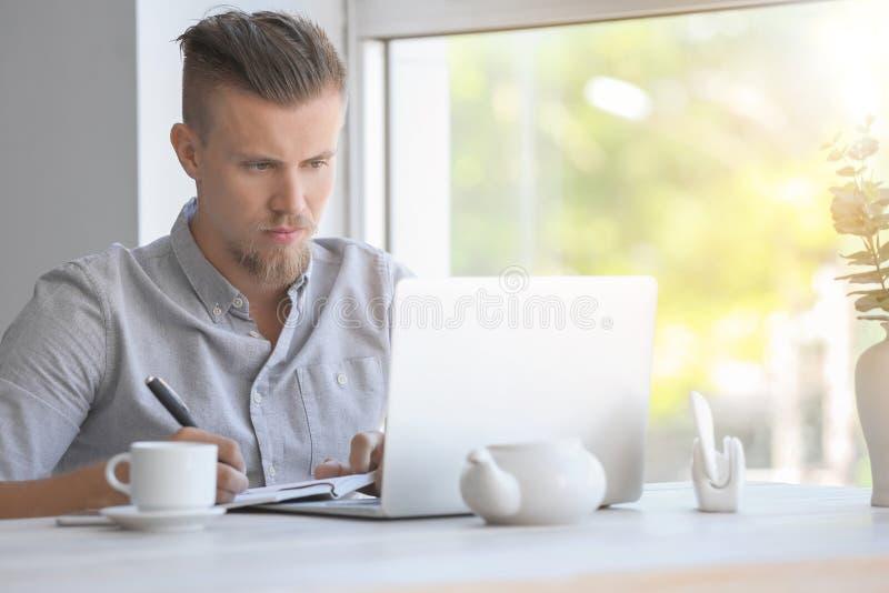 Knappe freelancer die aan laptop in koffie werken royalty-vrije stock fotografie