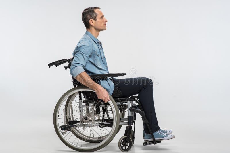 Knappe fysisch uitgedaagde mens die zich in rolstoel bewegen stock foto
