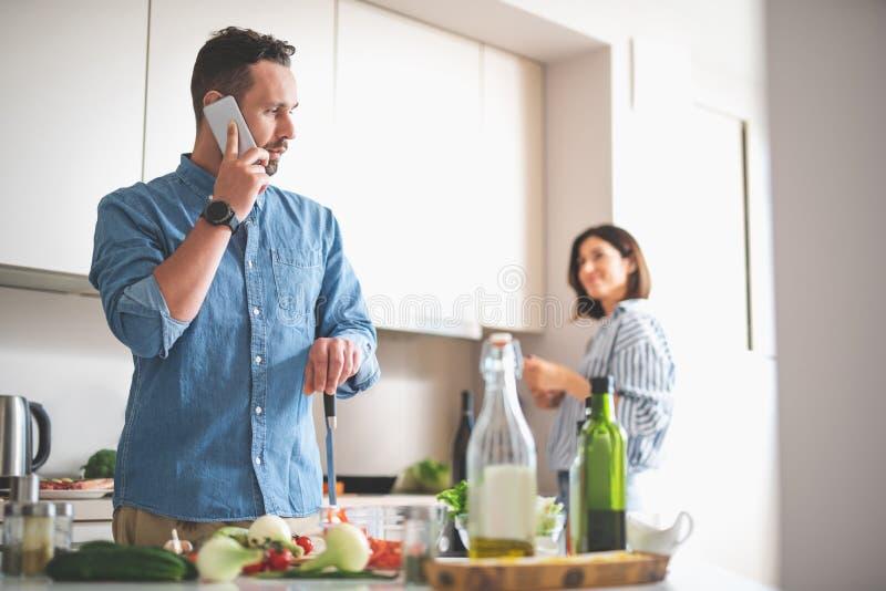 Knappe gebaarde heer die op cellphone in keuken spreken stock foto