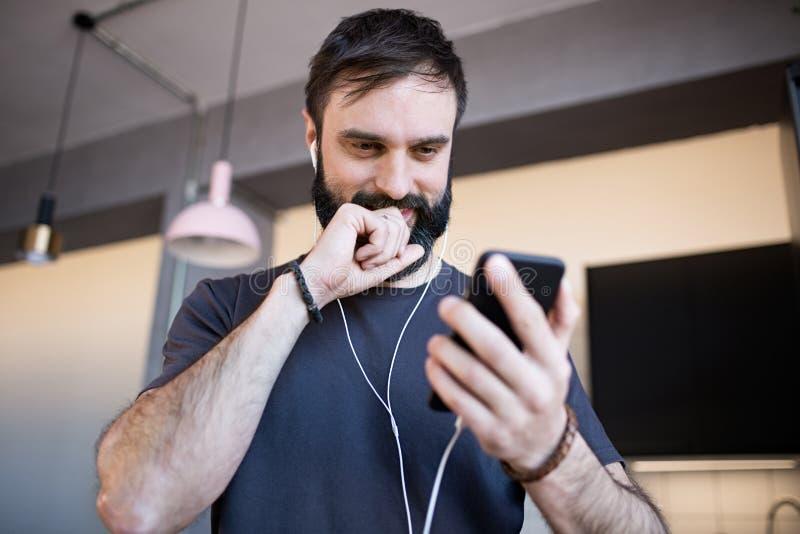 Knappe gebaarde kerel die toevallige grijze t-shirt het luisteren muziek in oortelefoons dragen, die sociale netwerken controlere stock afbeeldingen