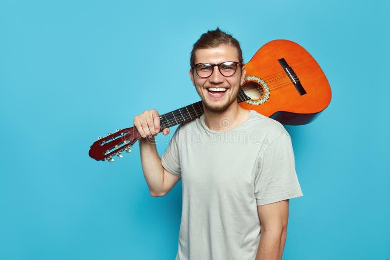Knappe gebaarde kerel met akoestische gitaar op schouder die en camera glimlachen bekijken terwijl status op heldere blauwe achte royalty-vrije stock fotografie