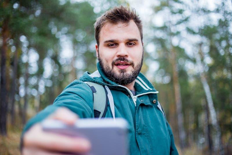 Knappe gebaarde mannelijke toerist die een selfie in een bos nemen royalty-vrije stock afbeelding