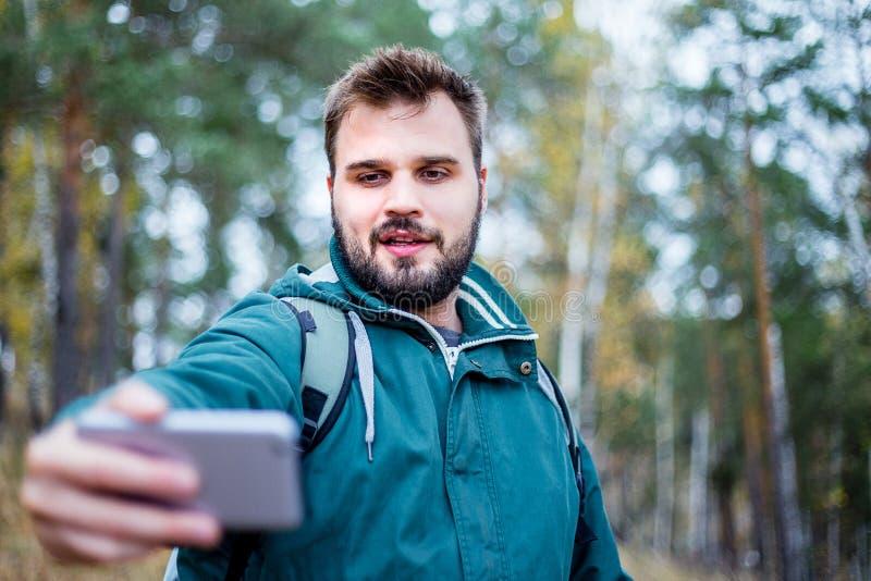 Knappe gebaarde mannelijke toerist die een selfie in een bos nemen stock foto