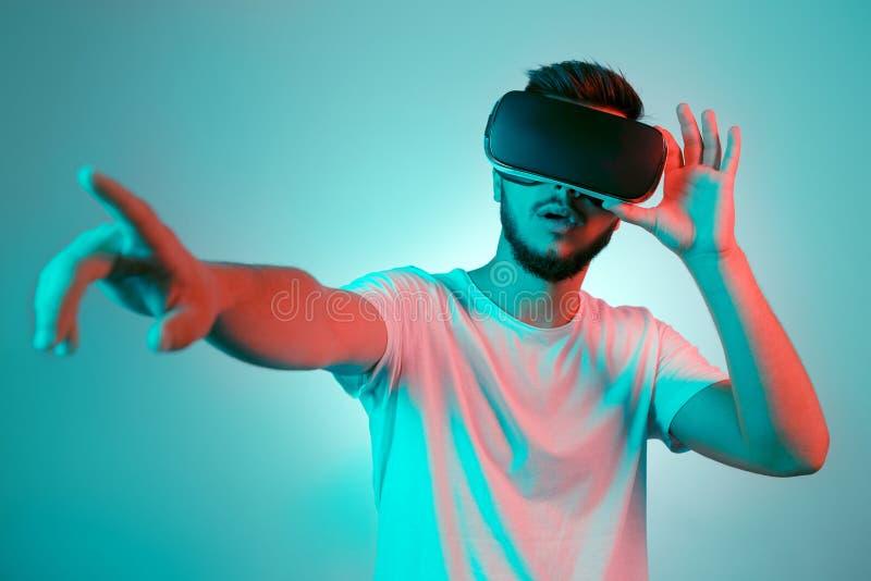 Knappe gebaarde mens die de hoofdtelefoon en het poniting van VR proberen Jonge mens die een andere wereld met virtuele werkelijk royalty-vrije stock afbeelding
