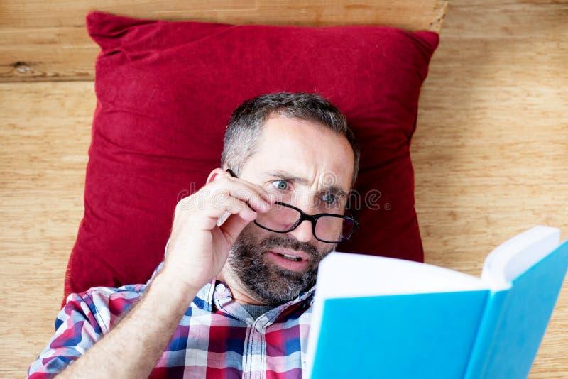 Knappe gebaarde mens die een boek lezen stock foto's