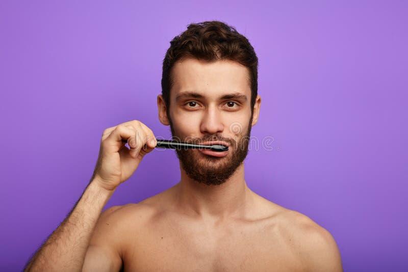 Knappe gebaarde mens die met tandenborstel in zijn mond de camera bekijken stock foto