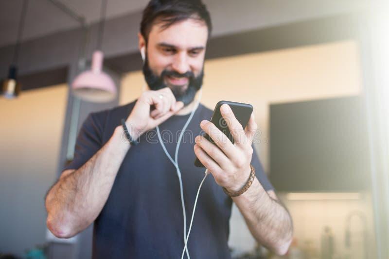 Knappe gebaarde mens het luisteren muziek bij modern huis Kerel die zich in moderne zolder, het houden van smartphonehand en het  royalty-vrije stock foto's