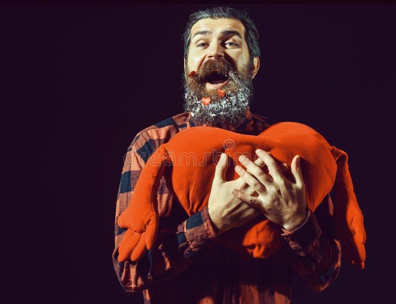 Knappe gebaarde mens of kerel in geruit overhemd met modieuze snor op gelukkig gezicht en rode verfraaide harten met stock foto's