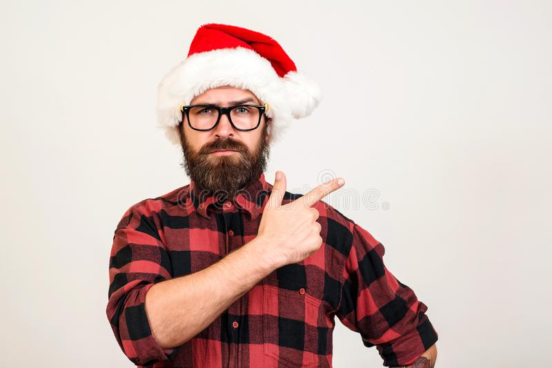Knappe gebaarde mens in Kerstmanhoed en glazen Kerstmanmens die aan de kant over witte muur richten Kerstmistak en klokken Spot o stock foto