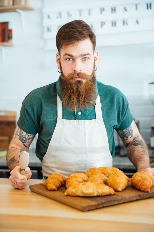 Knappe gebaarde mensenbarista met croissants in koffiewinkel royalty-vrije stock foto's
