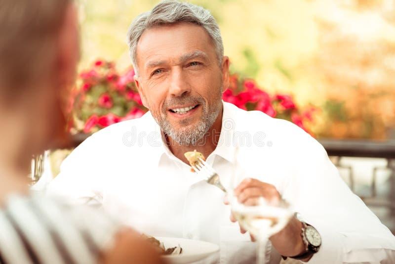 Knappe gebaarde rijpe mens die en aan zijn vrouw eten spreken royalty-vrije stock afbeelding