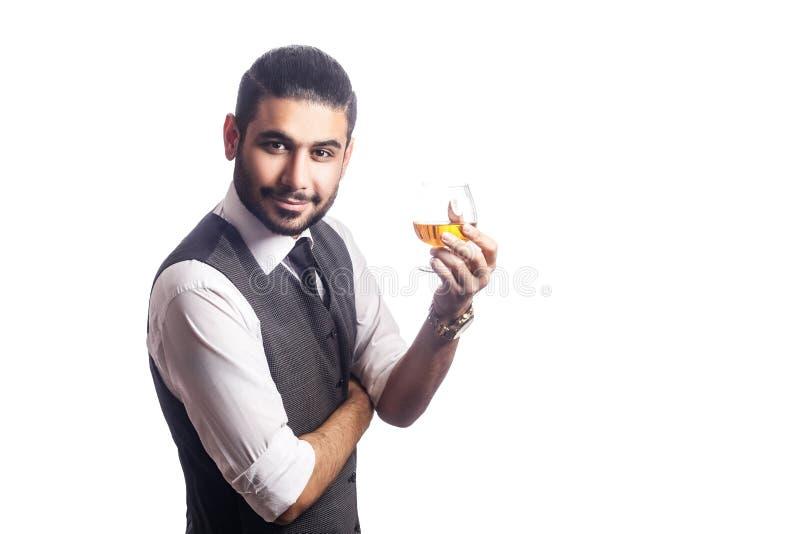 Knappe gebaarde zakenman die een glas whisky houden stock foto's