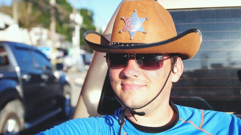 Knappe gelukkige cowboy in hoed en zonnebril die in een pick-up in zonnige dag reizen royalty-vrije stock foto's