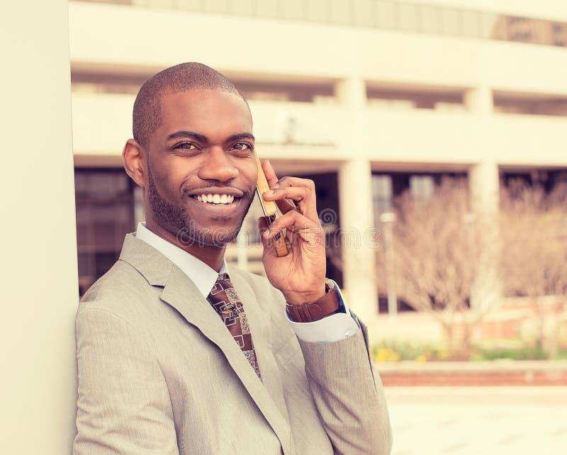 Knappe gelukkige jonge zakenman die op mobiele telefoon spreken stock foto's