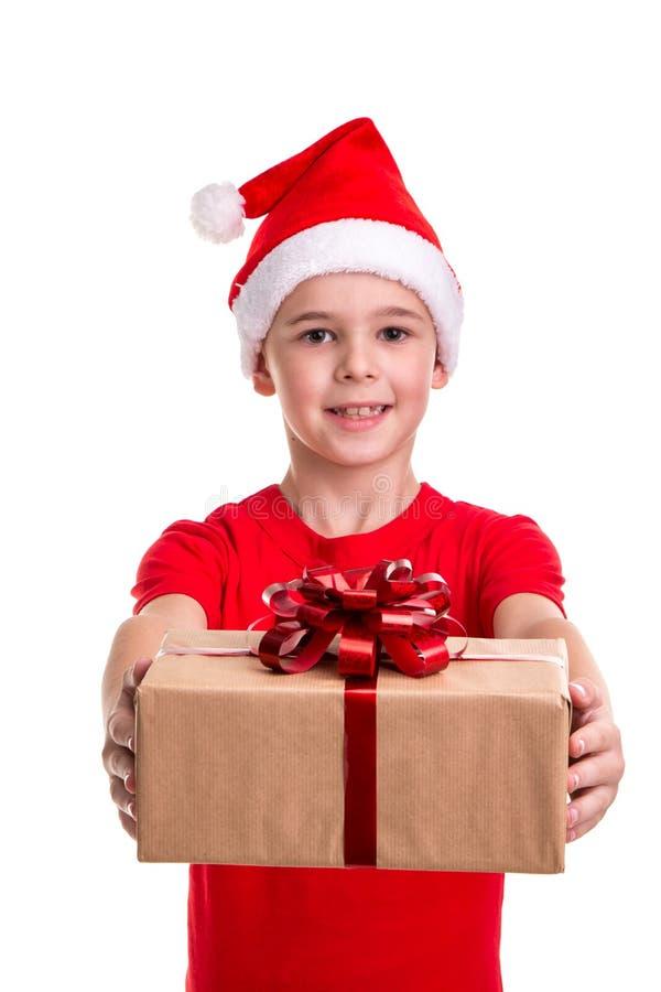 Knappe gelukkige jongen, santahoed op zijn hoofd, die de giftdoos standhouden Concept: Kerstmis of Gelukkige Nieuwjaarvakantie royalty-vrije stock afbeelding